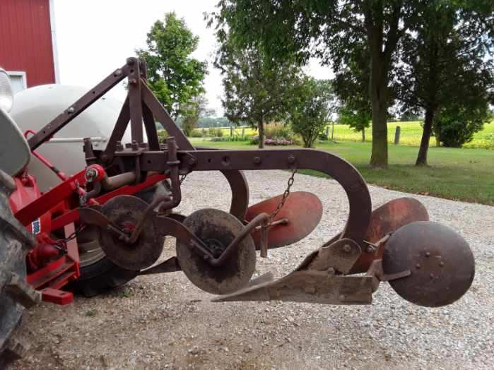 A 2 bottom plow mounted on an antique tractor
