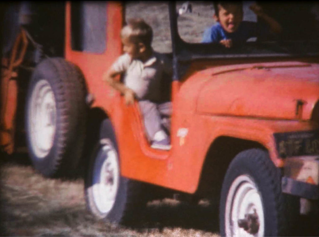 Two boys riding in a red Jeep