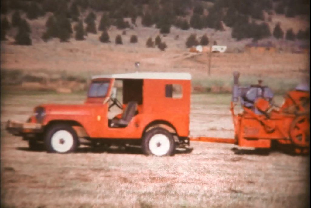 Red Jeep pulling a hay baler
