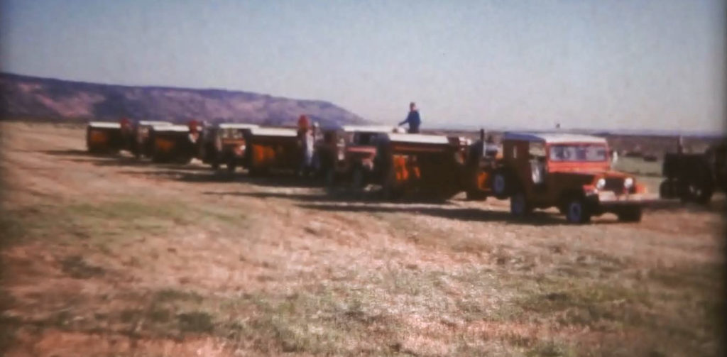 Jeeps towing hay balers in a row